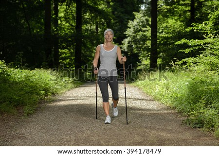 Nordic walking woman on tranquil forest path - stock photo