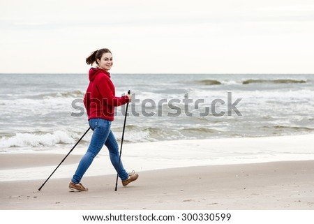 Nordic walking - young woman working out on beach  - stock photo