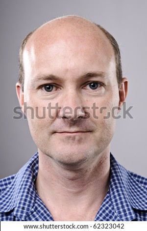 Normal bald man poses for portrait in studio - stock photo
