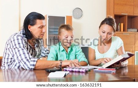 Normal  family of three doing homework in a home interior
