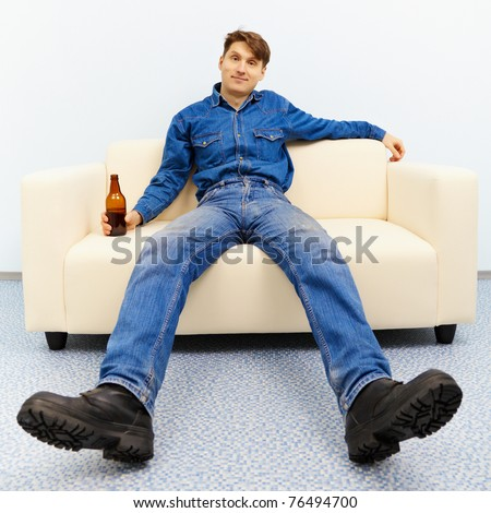 Normal inhabitant resting at home with a beer - stock photo