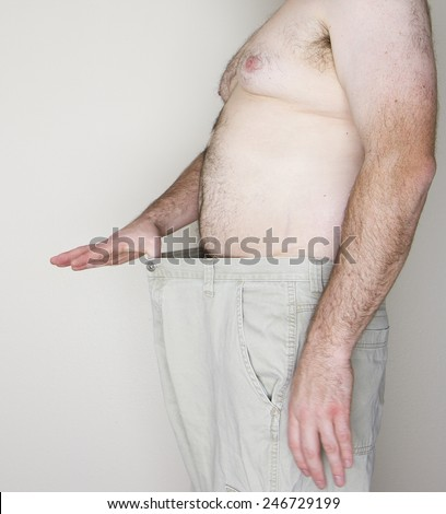 Normal looking obese man who has lost weight and fits into smaller jeans - stock photo