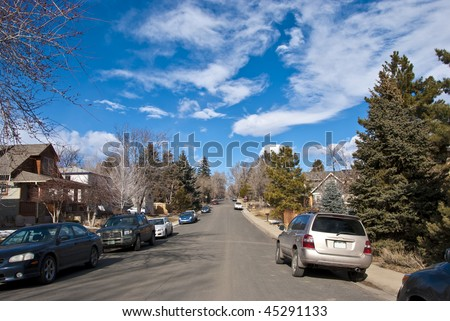 Normal suburban street scene on a peaceful and quiet day with interesting clouds - stock photo