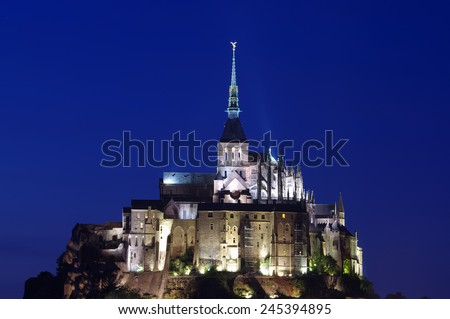 NORMANDY, FRANCE - SEPTEMBER 23, 2011: Night photo with long exposure of Mont Saint Michel, a castle part of the UNESCO list of World Heritage Sites. More than 3 million people visit it each year. - stock photo
