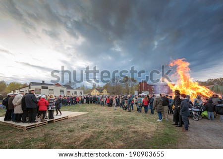 NORRTALJE - APR, 30, 2014: The traditional Valborg fire at Haverodal with a choir in the evening of April 30, 2014, Norrtalje, Sweden. Tradition in the Nordic countries to welcome the spring. - stock photo