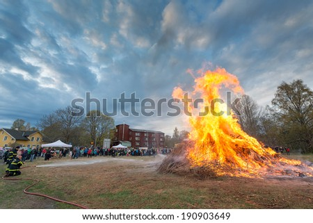 NORRTALJE - APR, 30, 2014: The traditional Valborg fire at Haverodal with firemen controlling the fire in April 30, 2014, Norrtalje, Sweden. Tradition in the Nordic countries to welcome the spring. - stock photo