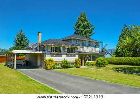 North American family house with big front yard and blue sky background. Family house with asphalt driveway and parking under roof.