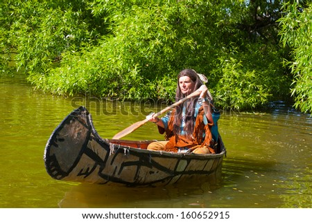 North American Indian floats down the river on a canoe - stock photo