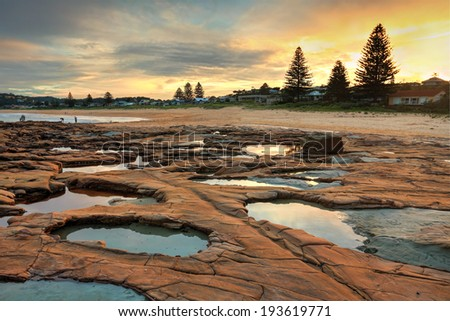 North Avoca.  The weathered crater like rock pools have a teal blue grey  colour in the rock while the surrounding surface rock is orange red.   Very surreal.  Focus to foreground - stock photo