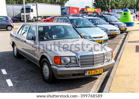 NORTH BRABANT, NETHERLANDS - AUGUST 9, 2014: Motor car Mercedes-Benz W126 S-class at the parking near the intercity highway. - stock photo