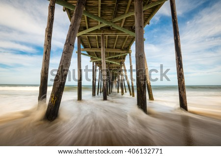 North Carolina Outer Banks Beach Seascape Nags Head OBX NC featuring ocean waves crashing into an old fishing pier on the beach - stock photo