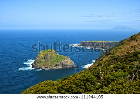 north coast of flores island with  single rock in front of the steep coast and corvo island in the background