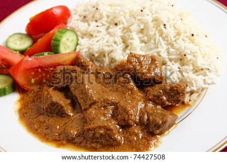 North Indian-style beef korma curry with basmati rice and a salad of tomato and cucumber - stock photo