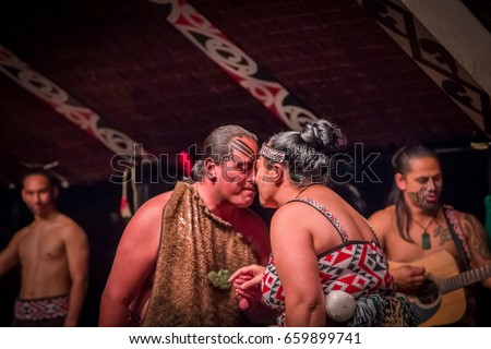 NORTH ISLAND, NEW ZEALAND- MAY 17, 2017: Tamaki Maori couple dancing with traditionally tatooed face in traditional dress at Maori Culture, Tamaki Cultural Village, in New Zealand