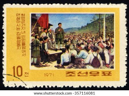 NORTH KOREA - CIRCA 1971: A stamp printed in North Korea dedicated to Revolutionary Activities of Kim Il Sung shows Kim with Crowd At Guerrilla Base Camp, circa 1971 - stock photo