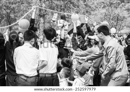 NORTH KOREA - MAY 1, 2012: Korean families pass under the skipping rope during the celebration of the International Worker's Day in N.Korea, May 1, 2012. May 1 is a national holiday in 80 countries - stock photo