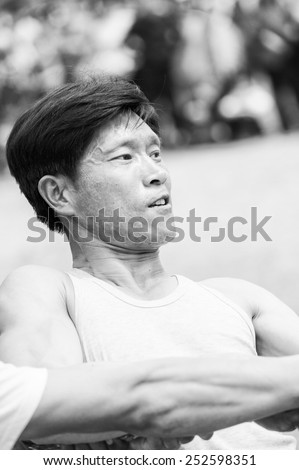 NORTH KOREA - MAY 1, 2012: Korean man actively participates in the tug of war game during the celebration of the Worker's Day in N.Korea, May 1, 2012. May 1 is a national holiday in 80 countries - stock photo