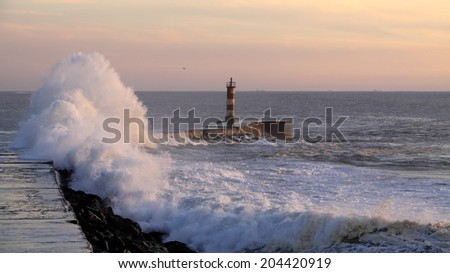 North of Portugal seascape in autumn seeing a big wave against a pier and lighthouse - stock photo