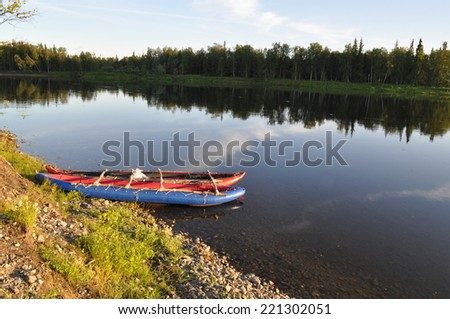 North of the Ural river in the evening light. Evening river landscape with a boat on the shore.