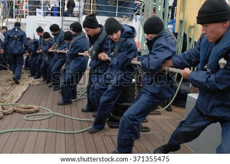 "NORTH VANCOUVER, CANADA - FEBRUARY 24, 2010: Cadets of Russian Bark ""Kruzenstern"" prepare the ship for sailing on Feb.24, 2010 in North Vancouver, Canada. - stock photo"