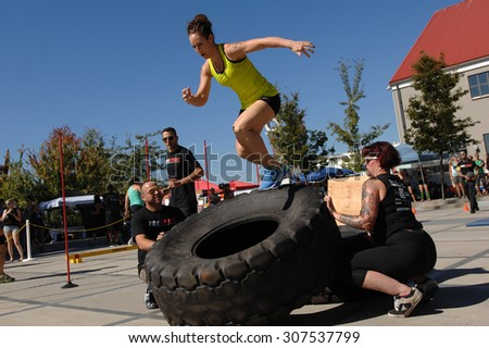 NORTH VANCOUVER, CANADA - SEPTEMBER 6, 2014: Female athletes show their strength during the FemSport Women's All Strength & Fitness promotional event on Sep.6, 2014 in North Vancouver, Canada. - stock photo