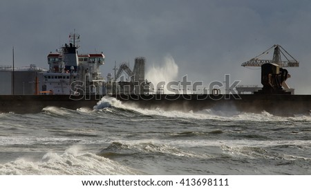 North wall of Leixoes harbor, north of Portugal, in wind and rough sea afternoon seeing a boat unloading chemicals - stock photo