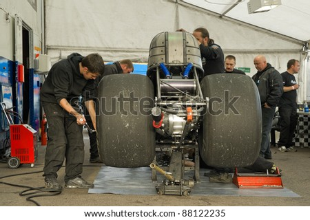NORTHAMPTONSHIRE, UK - OCT 29: Dragster mechanics completing extensive vehicle maintenance between races at the Flame and Thunder event on Oct 29, 2011 at Santa Pod Raceway in Northamptonshire, UK - stock photo