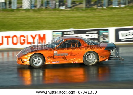 NORTHAMPTONSHIRE, UK  - OCT 29: Mazda RX dragster on the quarter mile strip at the Flame and Thunder race event on Oct 29, 2011 at Santa Pod Raceway in Northamptonshire, UK - stock photo