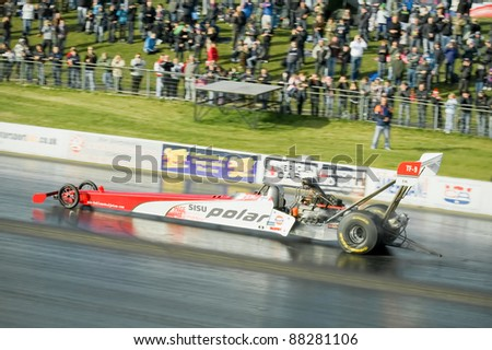 NORTHAMPTONSHIRE, UK - OCT 29: Wheelspin during a speed run by the 300mph Susi Polar top fuel dragster at the Flame and Thunder event on Oct 29, 2011 at Santa Pod Raceway in Northamptonshire, UK - stock photo