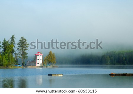 Northern Canada lake with lighthouse and a foggy background - stock photo