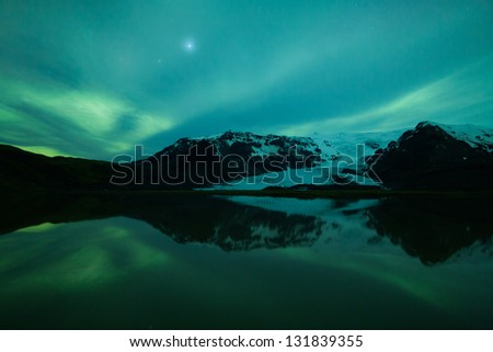 Northern lights (Aurora Borealis) above a glacier and lake in Iceland - stock photo