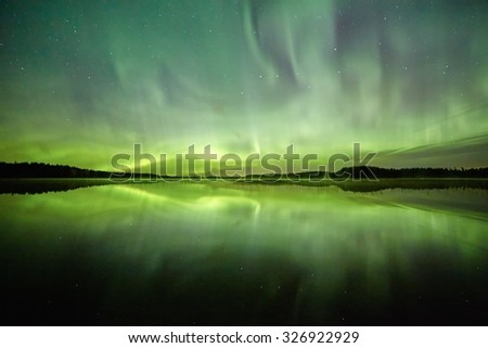 Northern lights (Aurora Borealis) above a lake with still water and reflections at night. Stars on the night sky behind the polar lights.