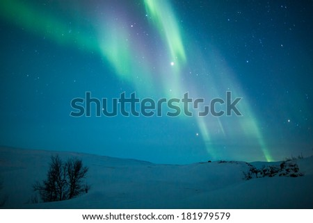Northern Lights Aurora Borealis above a snowy hill in Sweden - stock photo
