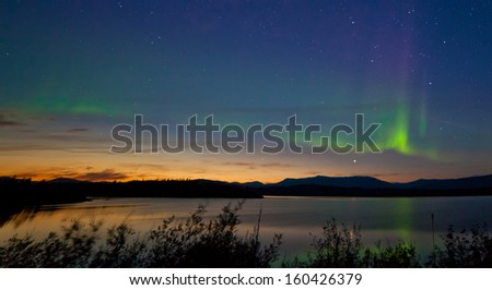 Northern lights  Aurora borealis  at midnight in summer over northern horizon of Lake Laberge  Yukon Territory  Canada  at early dawn - stock photo
