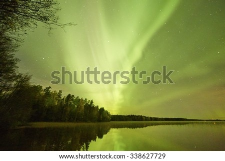 Northern lights (Aurora Borealis) glowing in the night sky over a beautiful lake in Finland. Vibrant colors on the sky and reflections on the still water of the lake. - stock photo