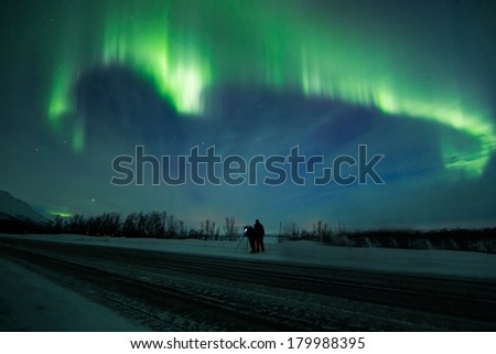 Northern lights (Aurora borealis) in Sweden above a people on a road - stock photo
