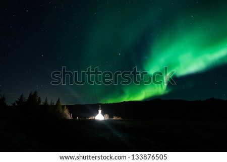 Northern lights (Aurora borealis) over Church in Iceland - stock photo