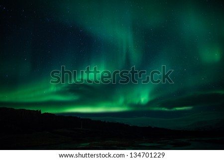 Northern Lights (Aurora Borealis) over lagoon in Iceland - stock photo