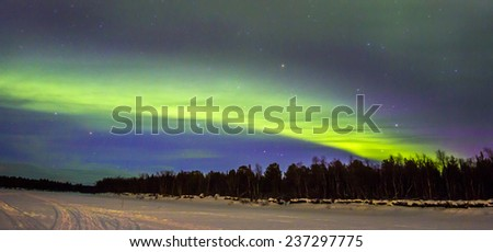 Northern Lights (Aurora borealis) over snowscape. - stock photo