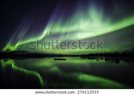 Northern lights blazing over lake Thingvellir national park in Iceland - stock photo