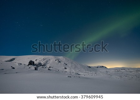 Northern lights in the sky over snow covered mountains - stock photo