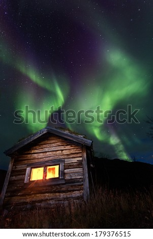 northern lights over a cabin in sweden - stock photo