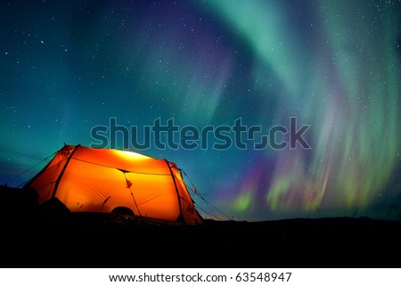 Northern lights over a illuminated tent in Lapland - stock photo