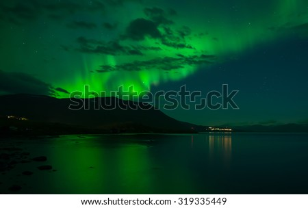 Northern lights over calm lake (Aurora borealis) in north of Sweden - stock photo