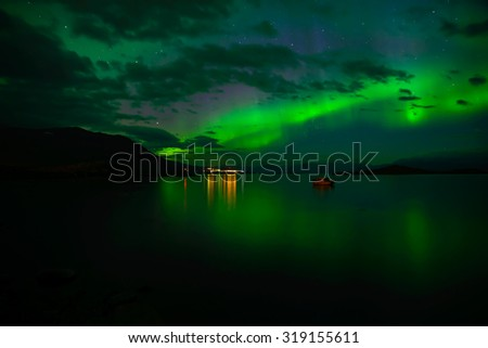 Northern lights over calm lake (Aurora borealis) in Sweden - stock photo