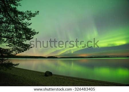 Northern lights over calm lake (Aurora borealis) in Sweden at Farnebofjarden national park, foreground unfocused - stock photo