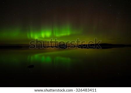 Northern lights over calm lake (Aurora borealis) in Sweden at Farnebofjarden national park - stock photo