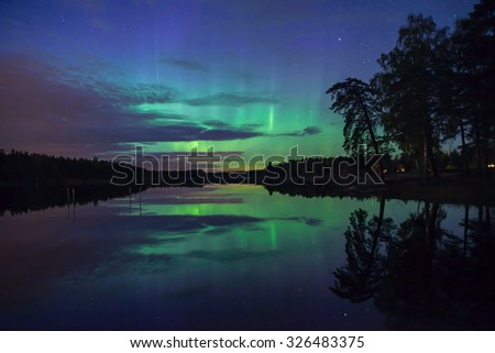 Northern lights over calm lake (Aurora borealis) in Sweden, unfocused trees - stock photo
