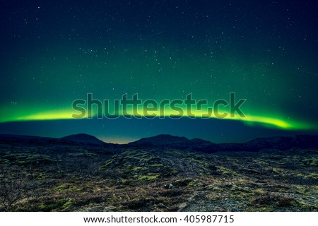 Northern lights over distant mountains in Iceland - stock photo