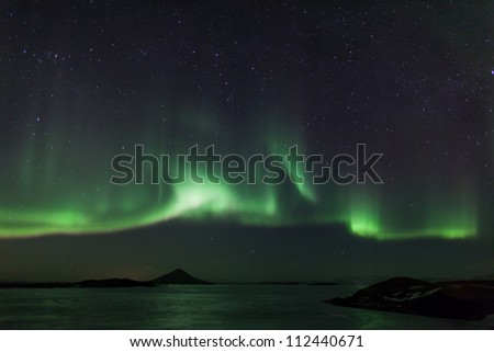 Northern lights over frozen lake Myvatn in Iceland - stock photo